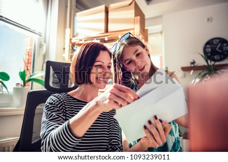 Mother and daughter sitting by the window and checking mail together at home office #1093239011