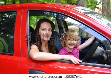 Mother and daughter sitting in a red car - stock photo