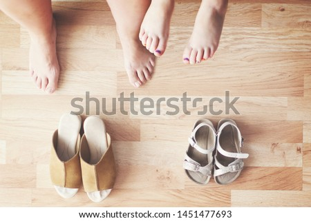 Mother and daughter sitting in the living room at home. Top view of barefoot legs and shoes on the barefoot feets and empty copy space for Editor's text.