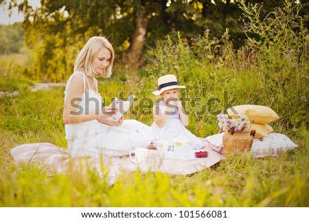Mother and daughter sitting on a blanket, mother reads the book, girl eats
