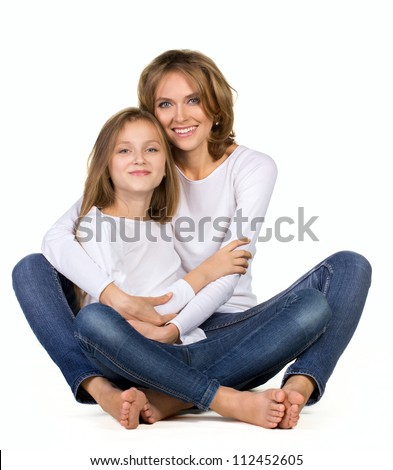 mother and daughter sitting on the floor and hugging each other isolated on white