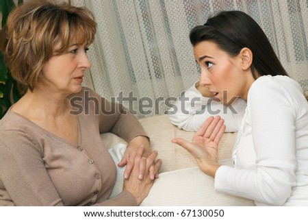 Mother and daughter sitting on the sofa and having a serious talking.