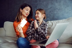 Mother and daughter sitting on the sofa and using laptop for online shopping. Daughter is begging for new toy she saw.