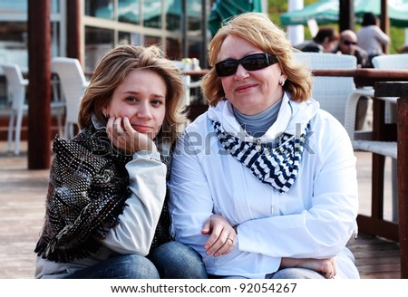 Mother and daughter sitting on the wooden steps to the cafe on the beach