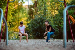 Mother and daughter sitting outdoor on a swing at the playground and having serious conversation
