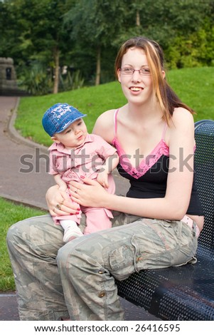 mother and daughter sitting outside on a park bench