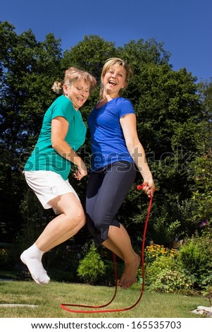 Mother and daughter skipping a rope