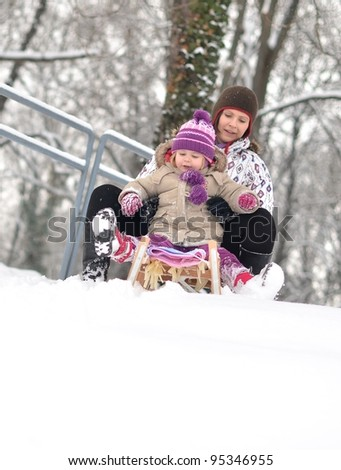 Mother and daughter sledging, nice winter scene
