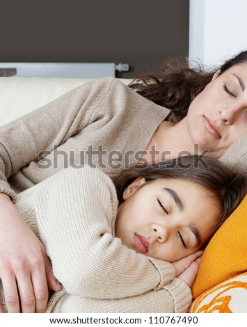 Mother and daughter sleeping on a white leather sofa at home.