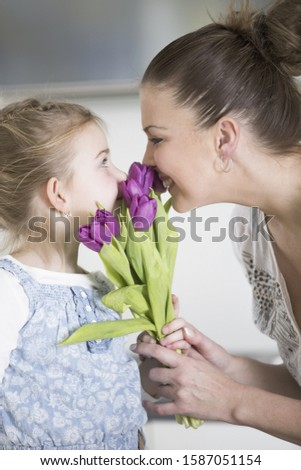 Mother and daughter smelling bunch of flowers