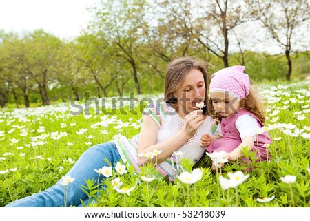 Mother and daughter smelling flower and enjoying time together