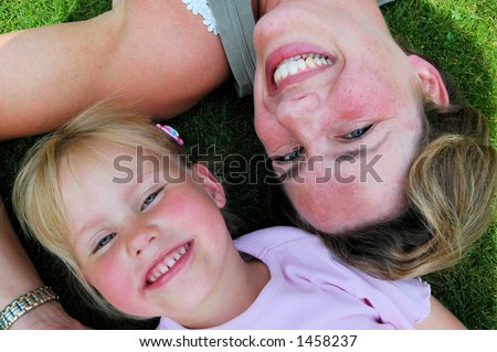 Mother and daughter smiling into the camera lens