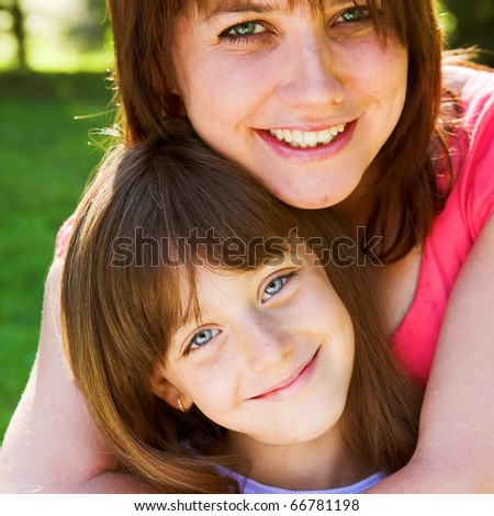 Mother and daughter smiling outdoor.