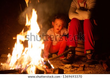 Mother and daughter spending quality time by a self-made campfire during adventurous camping trip, playing with fire. Active natural lifestyle, family time and love concept.  #1369693370