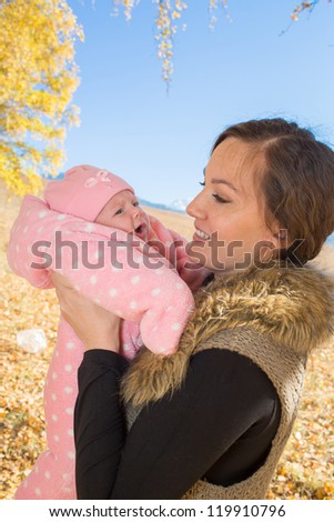 Mother and daughter spending time outdoor in the autumn park