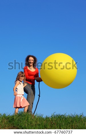 Mother and daughter stand in meadow with green grass against blue sky, one of which inflates yellow balloon with pump, while other keeps ball in his hands