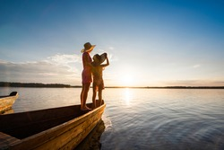 Mother and daughter stand together hugging on the bow of a wooden boat and enjoy the sunset by the lake or sea. Summer vacation near the water. Back view.