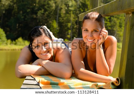 Mother and daughter sunbathing on pier smiling teen relaxing vacation