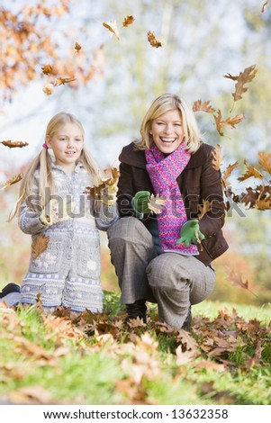 Mother and daughter throwing autumn leaves in the air