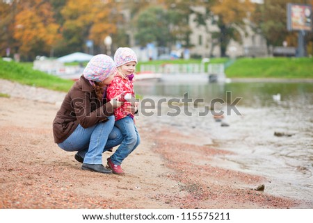 Mother and daughter together on beach by fall