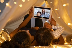 Mother and daughter using digital tablet while lying in kid tent doing a video call with father and son. Indian family in online conversation with each other during quarantine and social distancing.