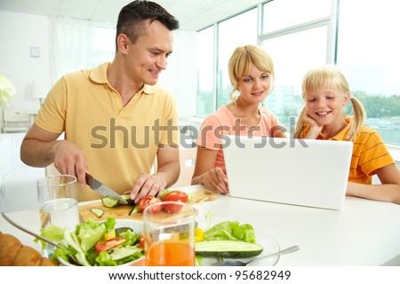 Mother and daughter using laptop while father cutting fresh vegetables
