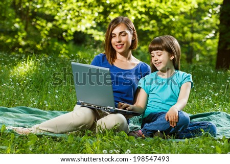Mother and daughter using laptop while sitting in the beautiful nature,Mother and daughter using laptop - stock photo
