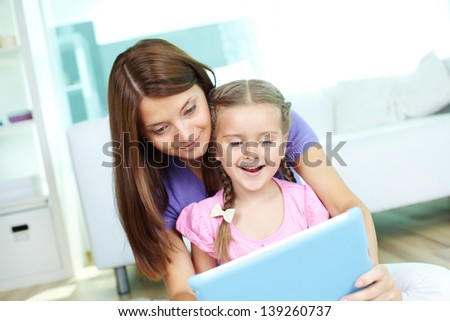 Mother and daughter using touchpad together at home