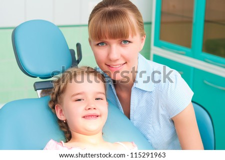mother and daughter visit the dentist, the child is sitting in the dental chair and mother near