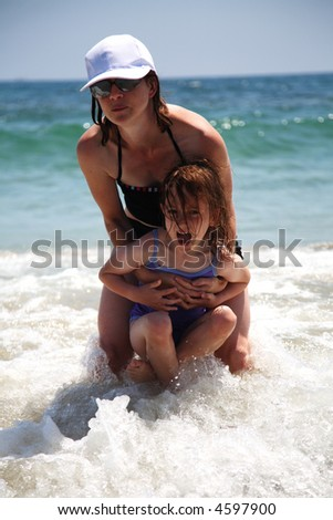 Mother and daughter waiting for the waves to crash over them