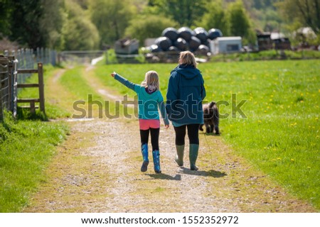 Mother and daughter walking a dog along a country track while the little girl points at something that interests her