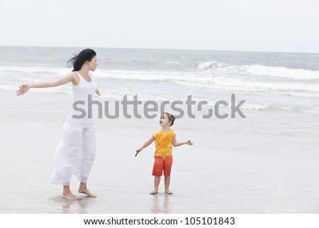 Mother and daughter walking along tropical beach - stock photo