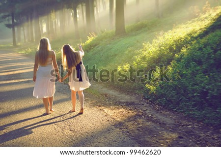 mother and daughter walking in the forest and holding hands - stock photo