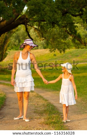 Mother and daughter walking in the nature on beautiful summer day.