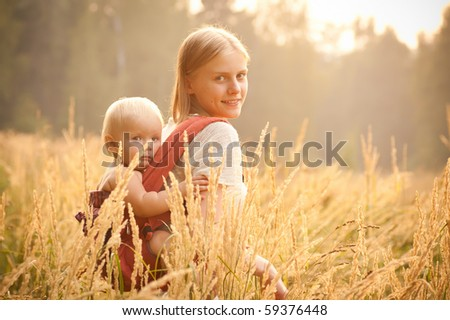 mother and daughter walking near forest by the road in the wheat field on sunset