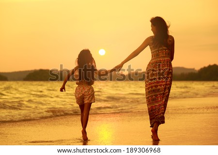 Mother and daughter walking on the beach with sunset