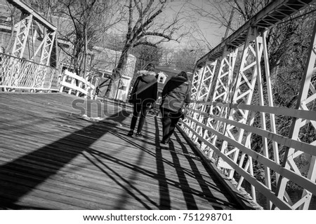 Mother and daughter walking on wooden and steel structure bridge. Female friend couple walking on walkway bridge. Light and shadow on industrial architectural bridge. Architecture and industrial art.