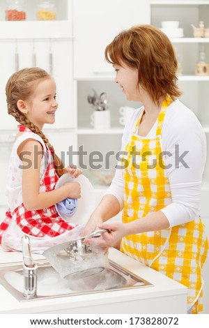Mother and daughter washing the dishes together and talking