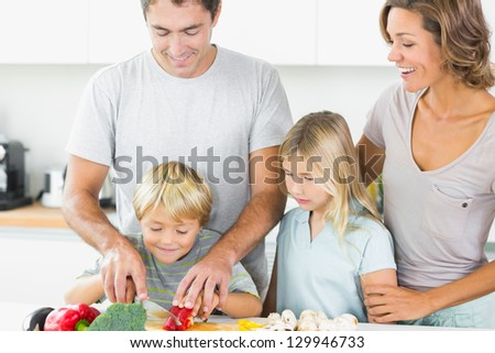 Mother and daughter watching father and son slicing vegetables in the kitchen