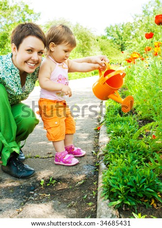 Mother and daughter watering flowers in the garden