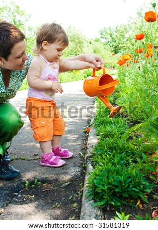 Mother and daughter watering plants in the garden