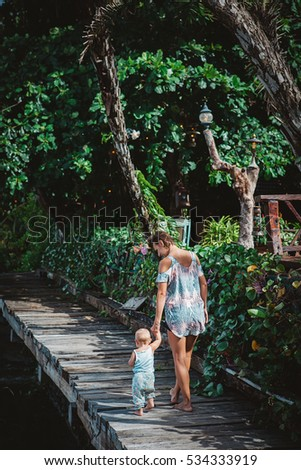 Mother and daughter wearing matching clothes with tropical print spending fun time outdoor during luxury family vacation