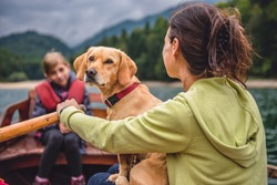 Mother and daughter with a small yellow dog rowing a boat on a mountain lake