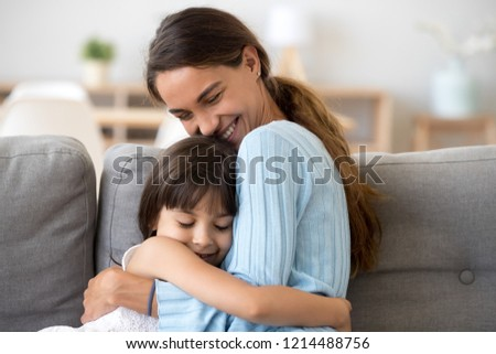 Mother and daughter with closed eyes sitting together on sofa at home embracing feels happy and satisfied. Beautiful female hug little child, motherhood warm relations new mum for adopted kid concept