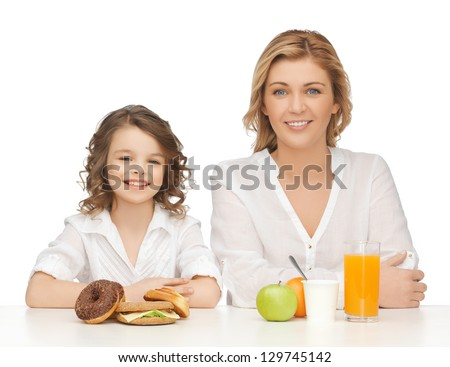 mother and daughter with healthy and unhealthy food