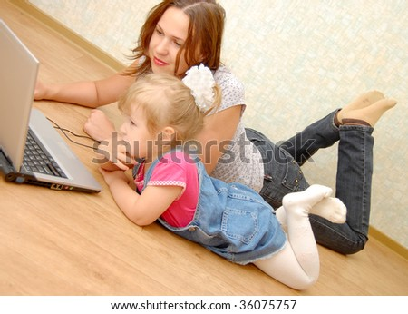 Mother and daughter with laptop on wooden  floor