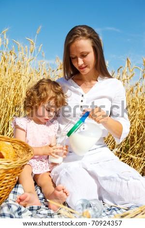 Mother and daughter with milk in the wheat field - stock photo