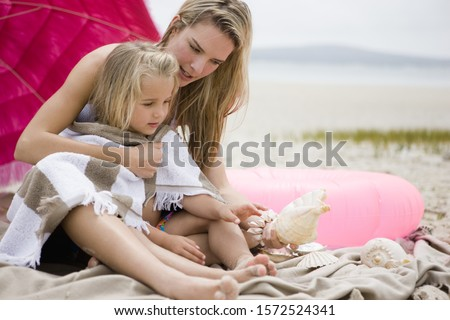Mother and daughter wrapped in blanket on beach