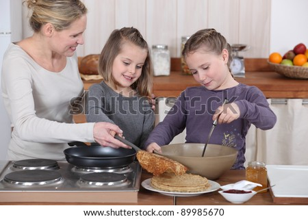 Mother and daughters making pancakes