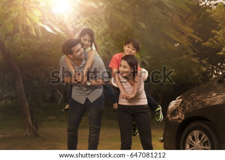 Mother and father carrying children on back in park